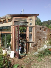 Eco-Sense Greenhouse with a rammed earth tire foundation built into the hillside.