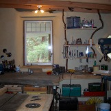 The Eco-Sense woodworking shop (in its cleaner days). all the shelves, windows, bench were found in the bush on the land.